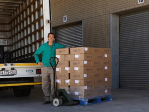Man standing beside boxes on pallet truck, with lorry, portrait